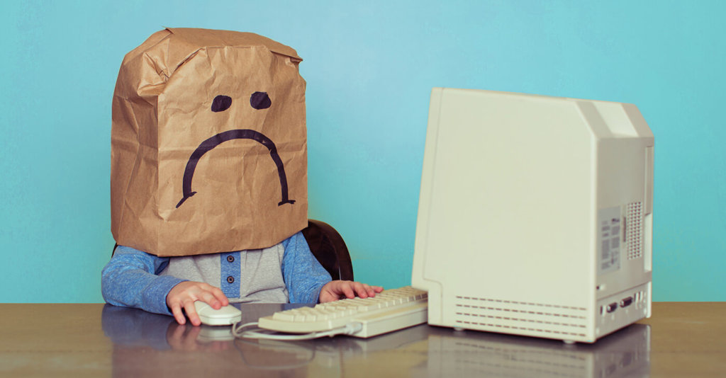 Unhappy bag boy at computer blue background
